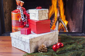 Colorful christmas presents at fireplace — Stock Photo