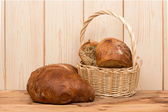 A fresh bread in the basket on the wooden background. — Foto de Stock