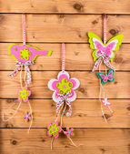 Spring decor -flower, bird and butterfly pendants on the wooden background. — Stock Photo