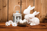 Easter decoration - ceramic easter rabbits and nest with eggs on the wooden background. — Stock Photo