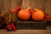 Pumpkins, red peppers and decorative  artificial autumn branches on the wooden background. — Stock Photo