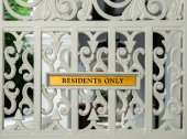 "Yellow sign ""RESIDENTS ONLY"" on white openwork gate — Stock Photo"