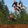 Motocross racers fly over jump — Stock Video #65525743
