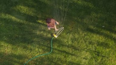 Child playing in sprinkler — Stock Video