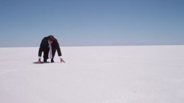 Businessman sprinting at salt flat — Stock Video