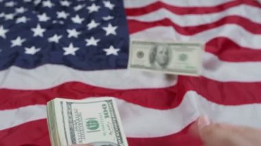 Person putting money on US flag — Stock Video