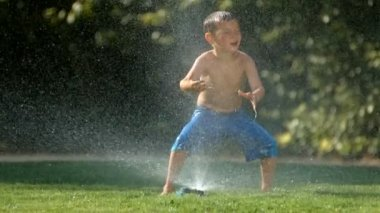 Kid jumping over sprinkler — Stock Video