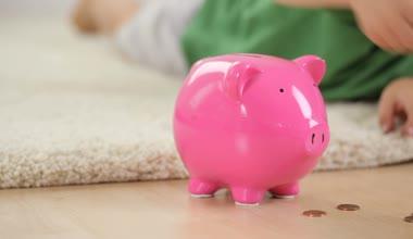 Boy putting money in piggybank — Stock Video