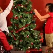 Family decorating Christmas tree — Stock Video #65609505