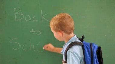 Boy writes on chalk board — Stockvideo
