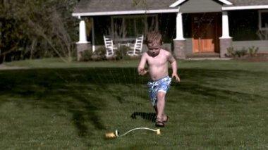 Boy running through sprinkler — Stock Video