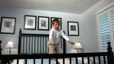 Boy jumps on bed — Stockvideo