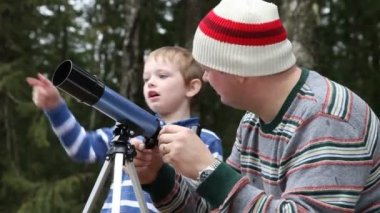 Father and son looking through telescope — Stock Video