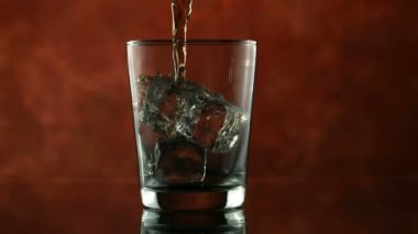 Whisky pouring over ice cubes — ストックビデオ