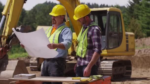 Trabajadores revisando planes — Vídeo de stock