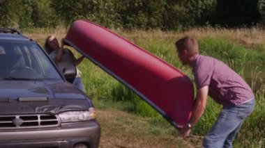 Unloading canoe off car — Stock Video