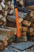 Axe with black and orange handle and firewood — Стоковое фото