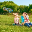 Mother with her two daughters in a park — Stock Photo #74352929