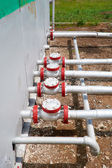 Oil pipelines from the pumping station belonging to the ground — Stock Photo