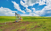 Pumping unit for pumping oil on a green meadow against a blue sky with clouds in summer — Stock Photo
