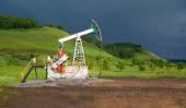 Unidad de bombeo para bombear el aceite en una nubes oscuras de tormenta azul — Foto de Stock