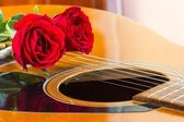 Acoustic guitar and roses — Stock Photo