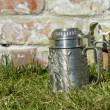 Two beer mugs on the grass near the brick wall — Stock Photo #67991537