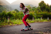 Teenage girl longboarding in mountains — Stok fotoğraf