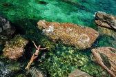 Girl in bikini swimming in the sea aerial top view — Stock Photo
