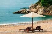 Two sunbeds  and umbrella at luxury beach resort — Stock fotografie