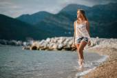 Dreamy fashion girl walk on beach with mountains background — Stock Photo
