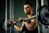 Strong bodybuilder athlete portrait  with heavy  weights in gym — Stok fotoğraf