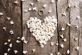 Gentle white heart shape flowers with ring on wood table — Stock Photo