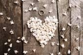 木のテーブルにリングと穏やかなホワイト ハート形花 — ストック写真