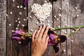 Heart shape of white lilac flowers and hand with ring on wood ta — Stock Photo