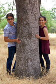 Teenage boyfriend and girlfriend in a park next to a tree — Stock Photo