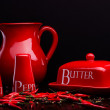 Red salt-cellar, pepper-box, butter and pitcher set on dark background by Cristina Arpentina — Stock Photo #67017171