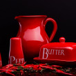 Red salt-cellar, pepper-box, butter and pitcher set on dark background by Cristina Arpentina — Stock Photo #67017183