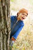 Little boy peeping from behind a tree. — Stock Photo