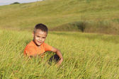 Young boy resting sitting in tall grass. — Stock Photo