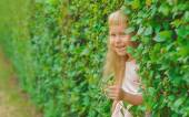 Girl hiding in green bushes — Stock Photo