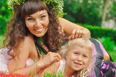 Girl and mommy in grass — Stock Photo