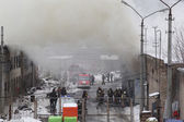 Firefighters extinguish a warehouse. The building is in smoke — Stock Photo