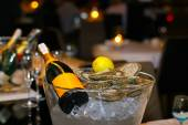 Champagne bottle with lemon and fresh oysters in a bucket with ice — Fotografia Stock