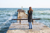Girl standing on a pier looking into the distance — Stockfoto