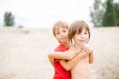 Fraternal twins hugging at the beach — Stock Photo