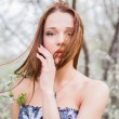 Red-haired young woman in spring orchard — Stock Photo #70084897