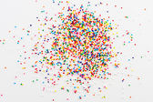 Colorful round sprinkles spilled on white background, isolated — Stock Photo