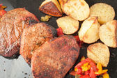 Succulent thick juicy portions of grilled fillet steak served with roasted potatoes and peppers on black granite board — Stock Photo