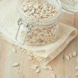 Hulled sunflower seeds in glass jar on wooden rustic background — Stock Photo #68051677
